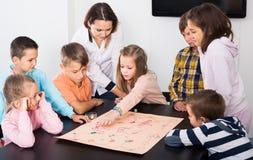 Bambini elementari di calma di età alla tavola con il gioco da tavolo ed i dadi immagini stock