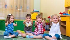 Bambini emozionanti che tengono i pollici su Immagini Stock Libere da Diritti