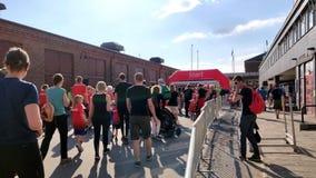 Bambini energetici che vanno ad un punto dichiarante per un evento che indossa jercey rosso in un giorno soleggiato archivi video
