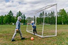 Bambini in età prescolare che giocano a calcio sul prato inglese immagini stock libere da diritti