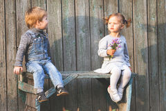 Bambini felici all'aperto alla stagione di caduta, sedentesi al banco Prima data Fotografie Stock Libere da Diritti