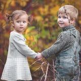 Bambini felici all'aperto alla stagione di caduta, tenentesi per mano Ha data Immagine Stock