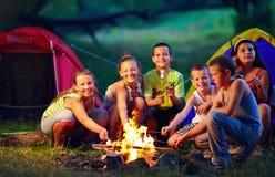 Bambini felici che arrostiscono le caramelle gommosa e molle su fuoco di accampamento fotografie stock libere da diritti