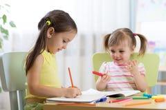 Bambini felici che assorbono la stanza della scuola materna Immagini Stock