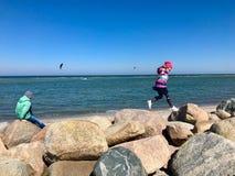 Bambini felici che camminano e che esaminano gli sport acquatici una spiaggia immagini stock libere da diritti