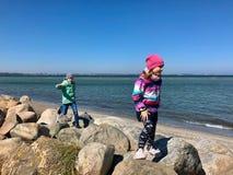 Bambini felici che camminano e che esaminano gli sport acquatici una spiaggia fotografia stock libera da diritti