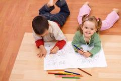 Bambini felici che colorano il libro di racconto Immagine Stock