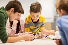 Bambini felici che costruiscono i robot alla scuola di robotica Immagini Stock