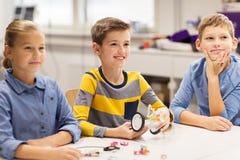 Bambini felici che costruiscono i robot alla scuola di robotica Immagine Stock