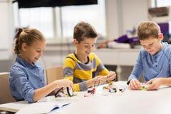 Bambini felici che costruiscono i robot alla scuola di robotica Immagine Stock Libera da Diritti