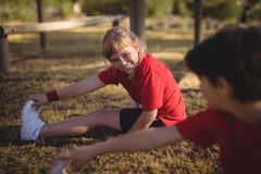 Bambini felici che eseguono allungando esercizio durante la corsa ad ostacoli immagine stock libera da diritti