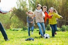 Bambini felici che giocano a calcio all'aperto Fotografie Stock