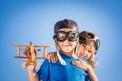 Bambini felici che giocano con l'aeroplano del giocattolo immagine stock