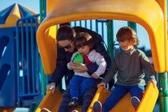 Bambini felici che giocano nel parco con la loro madre immagini stock