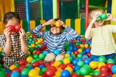 Bambini felici che giocano nel pozzo della palla immagine stock libera da diritti
