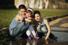 Bambini felici che giocano nella pozza Fotografia Stock Libera da Diritti