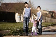 Bambini felici che giocano nella pozza Fotografie Stock Libere da Diritti