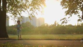 Bambini felici che guidano i motorini e le bici di scossa nel parco insieme ai genitori video d archivio