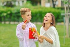 Bambini felici che mangiano gli ortaggi freschi in natura - bambini sorridenti che dividono i bio- peperoni variopinti affettati  fotografia stock libera da diritti