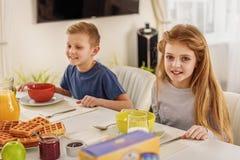 Bambini felici che mangiano le cialde dolci in cucina Fotografia Stock