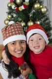 Bambini felici che pongono sotto l'albero di Natale Fotografie Stock