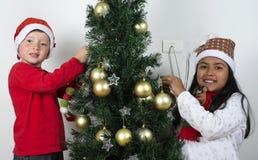 Bambini felici che pongono sotto l'albero di Natale Fotografia Stock Libera da Diritti