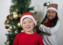 Bambini felici che pongono sotto l'albero di Natale Immagini Stock Libere da Diritti