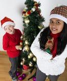 Bambini felici che pongono sotto l'albero di Natale Immagine Stock