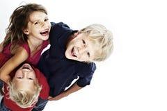 Bambini felici che ridono e che osservano in su Fotografie Stock Libere da Diritti