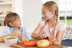 Bambini felici che sbucciano le verdure in cucina Immagini Stock