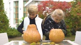 Bambini felici che scolpiscono la presa-o-lanterna della zucca, preparante per il partito di Halloween archivi video