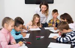 Bambini felici che si siedono alla tavola con il gioco da tavolo ed i dadi Fotografia Stock Libera da Diritti