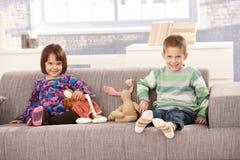 Bambini felici che si siedono sul sofà Fotografia Stock
