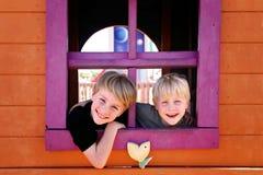 Bambini felici che sorridono al parco come danno una occhiata fuori alla finestra di una fortificazione del circolo fotografia stock