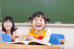 Bambini felici che studiano in un'aula Immagini Stock