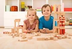 Bambini felici con i blocchi di legno sul pavimento Immagine Stock Libera da Diritti