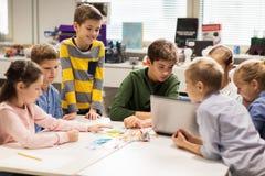 Bambini felici con il computer portatile alla scuola di robotica Immagine Stock
