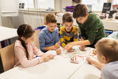 Bambini felici con il corredo di invenzione alla scuola di robotica fotografie stock