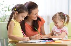 Bambini felici con l'insegnante che assorbe aula Immagine Stock