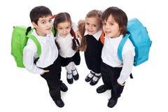 Bambini felici del banco con i pacchetti posteriori Fotografia Stock Libera da Diritti