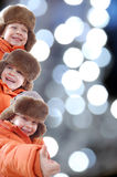 Bambini felici di inverno contro gli indicatori luminosi variopinti Fotografie Stock