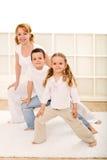 Bambini felici e donna che fanno le esercitazioni di ginnastica Fotografia Stock