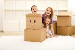 Bambini felici e donna che hanno divertimento nella loro nuova casa immagini stock
