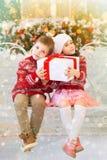 Bambini felici ragazza e regalo della tenuta del ragazzo per il Natale Immagine Stock