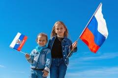 Bambini felici, ragazze sveglie con la bandiera della Russia contro un chiaro cielo blu immagini stock