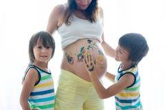 Bambini felici, ragazzi, dipingenti sulla pancia incinta del ` s della mamma Fotografia Stock