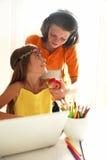 Bambini felici a scuola con un computer portatile Immagini Stock Libere da Diritti
