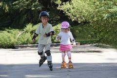 Bambini felici sulle lamierine del rullo all'aperto fotografia stock