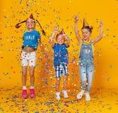Bambini felici in vacanza che saltano nei coriandoli multicolori su giallo fotografie stock