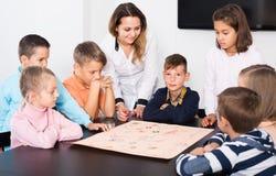 Bambini femminili e felici che si siedono alla tavola con il gioco da tavolo Fotografia Stock